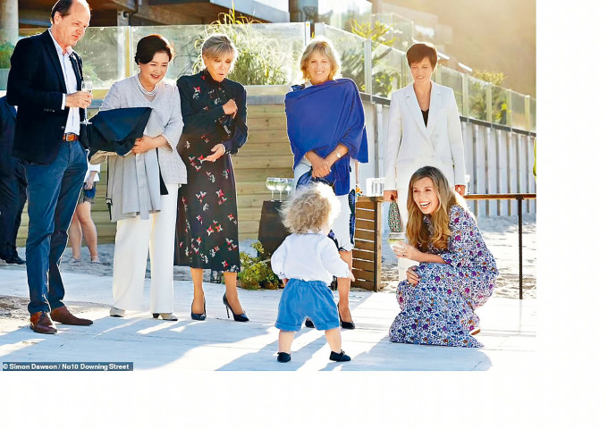 約翰遜夫人西蒙兹(右)與兒子威爾弗雷德現身沙灘燒烤會場,一眾G7與會領袖的伴侶展現笑顏。