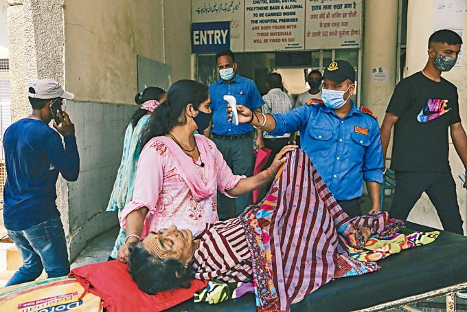 印度查謨一名陪診女子,周一進入政府醫院前檢查體溫。