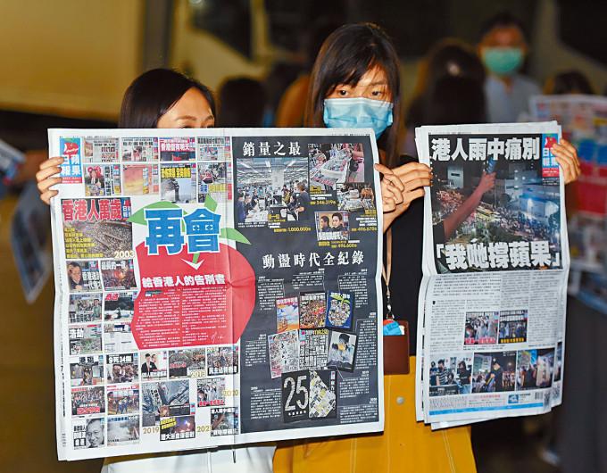 今晨零時許有《蘋果》員工走出大樓,展示剛印好出版的告別版《蘋果日報》。