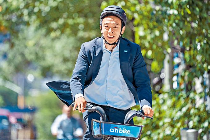 華裔參選人楊安澤上周三騎單車前往票站提早投票。