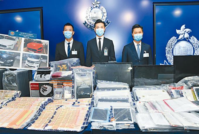 署理總警司何振東(中)講述案情,並展示檢獲的現鈔及電腦等證物。