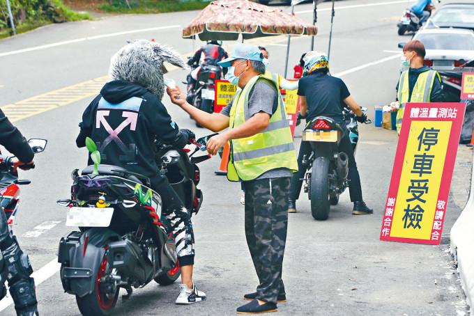 台灣桃園市路口有管制站測量入區人員體溫。