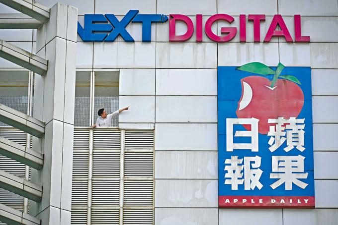 員工與大樓蘋果巨型標誌拍照留影。