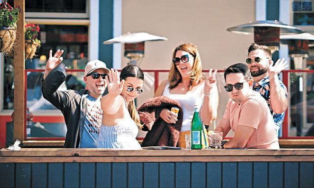 意大利區酒吧的遊客揮手示意。                           記者黃偉江攝
