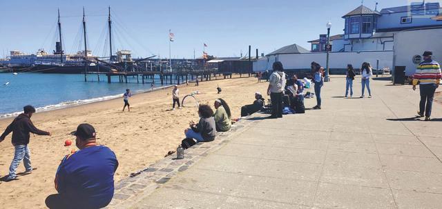 ■漁人碼頭海灘很久未見的遊客群。記者李兆庭攝