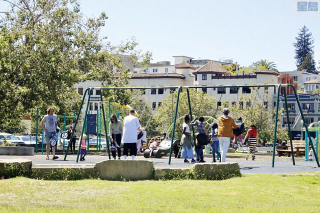父親節周日,屋崙市美麗湖附近的兒童公園內,家長和孩子一起玩耍,一起使用鞦韆和其他遊玩設施。 記者張曼琳攝