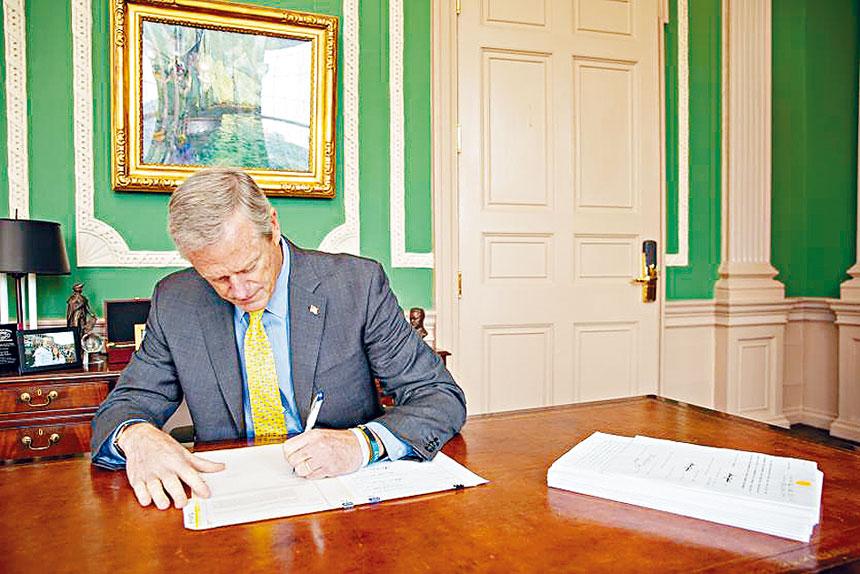 州長查理貝克在簽署2022財年預算。州政府供圖