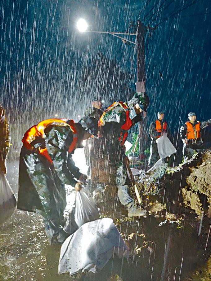 解放軍空降兵冒雨加固河堤。