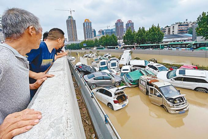 數十輛汽車被洪水衝擠在一起。